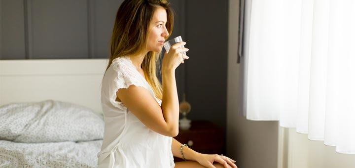 Une femme buvant de l'eau sur un lit