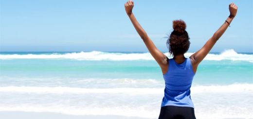 black-woman-arms-up-on-beach