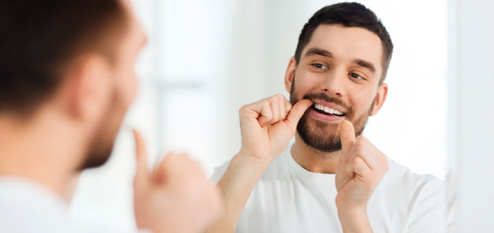 man-flossing-in-mirror