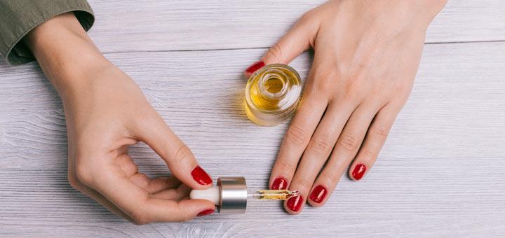 woman-applying-nail-oil