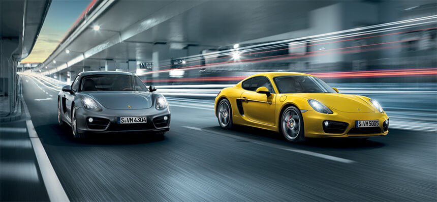 Two Porsche Cayman's driving through city