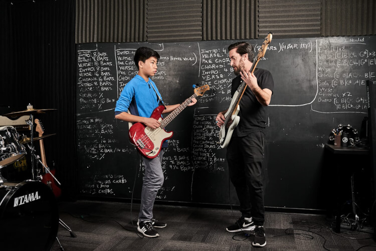 Instructor and student taking advanced bass guitar lessons
