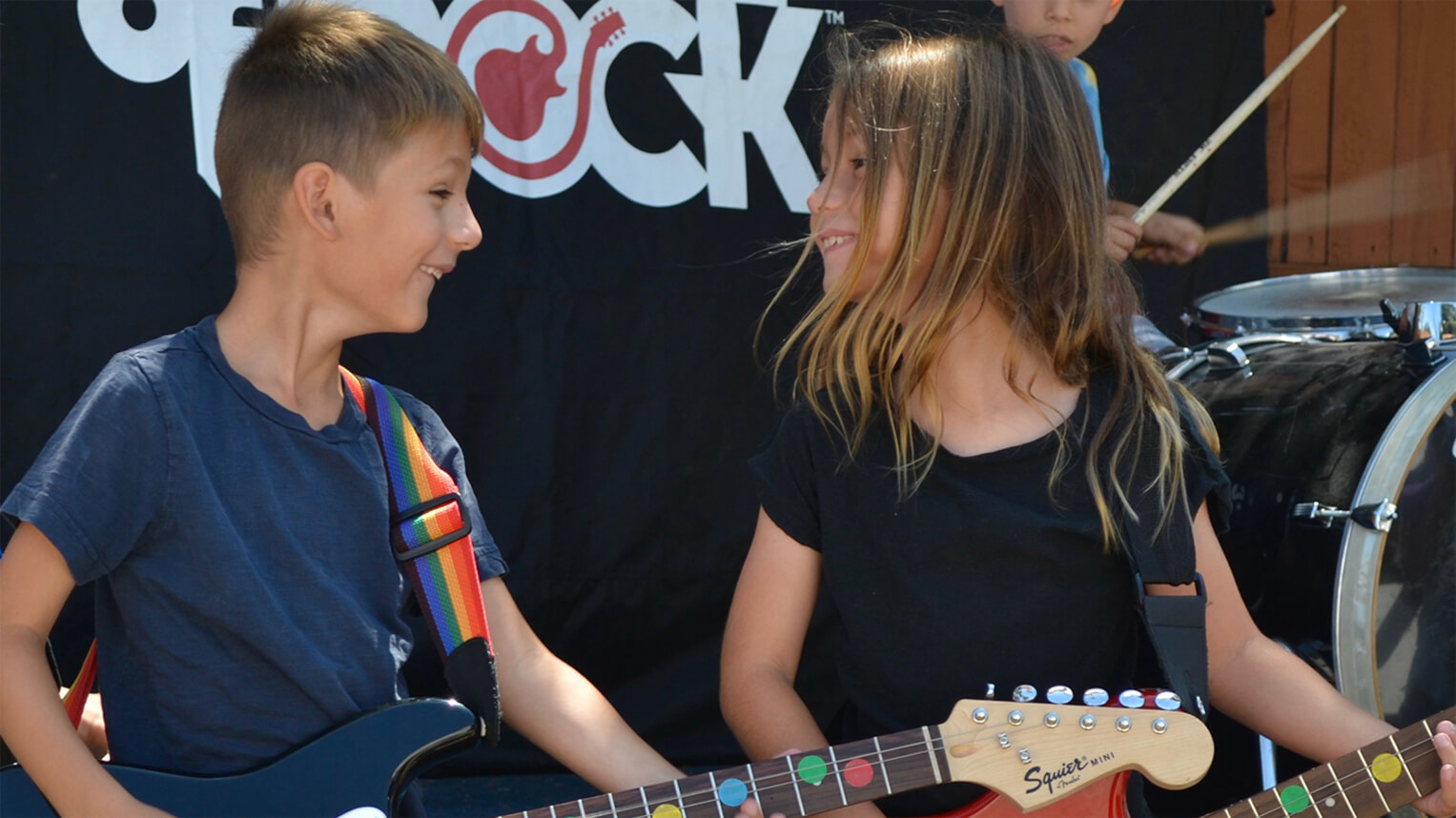 summer camp, guitar lessons, bass lessons, no experience needed, drum lessons, guitarists looking at each other, rock out on stage, kid playing guitar