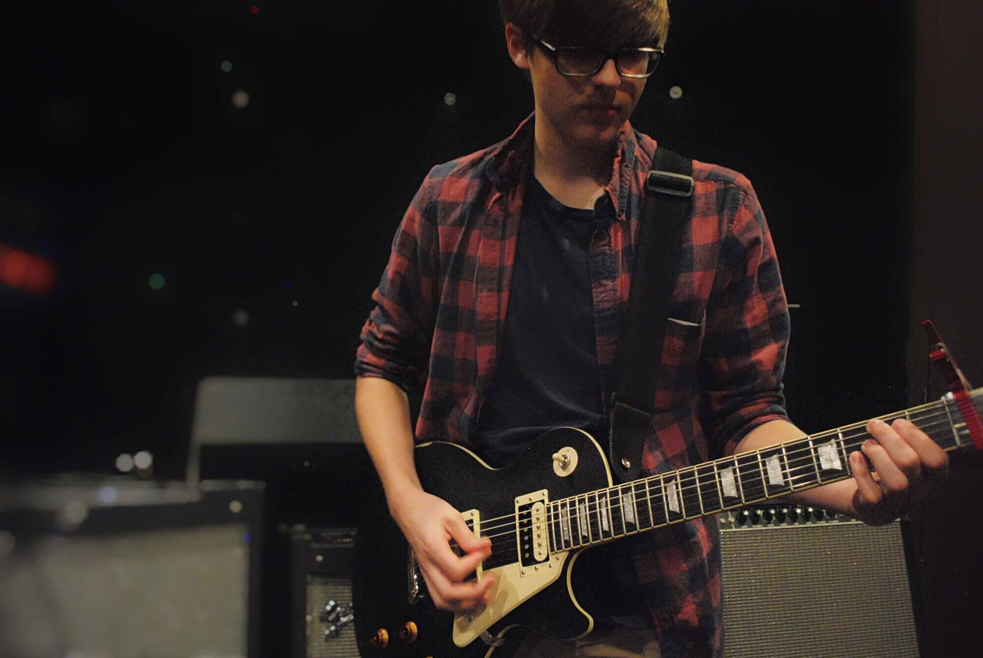 A School of Rock Katy House Band student runs through his guitar part during rehearsal.