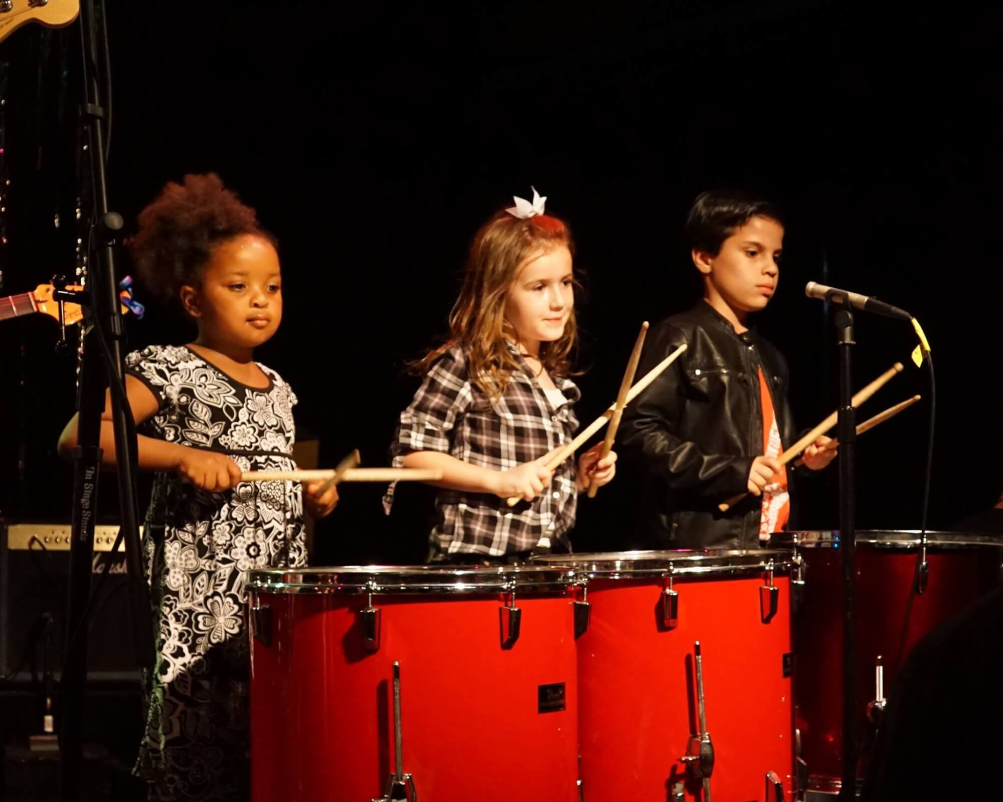 Rookies students play drums in the Queen show.