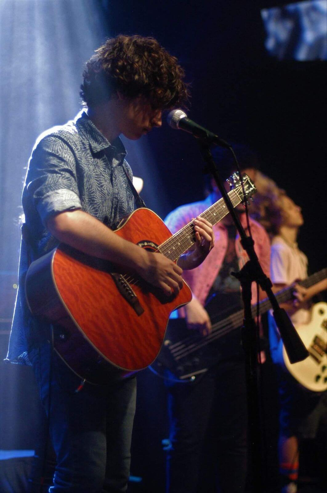 Paul Nameth playing acoustic guitar on the House Band Tour.