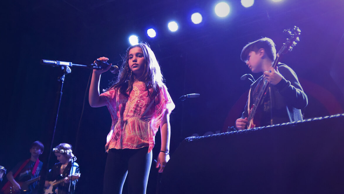 Uma takes the mic for her Rock 101 band's end of season show.