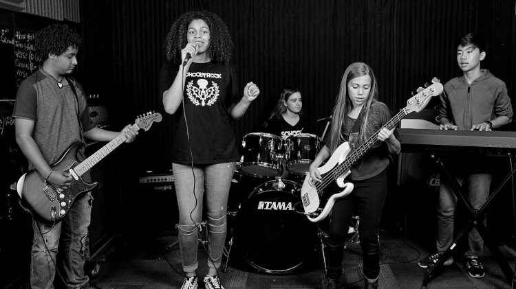 School of Rock students play music on stage and in a band in our music programs