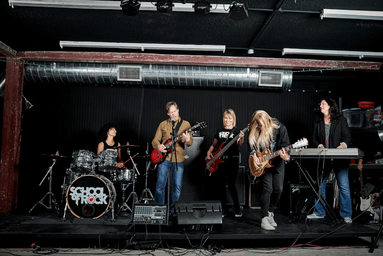 Students playing onstage in School of Rock's Adult Performance Music Program