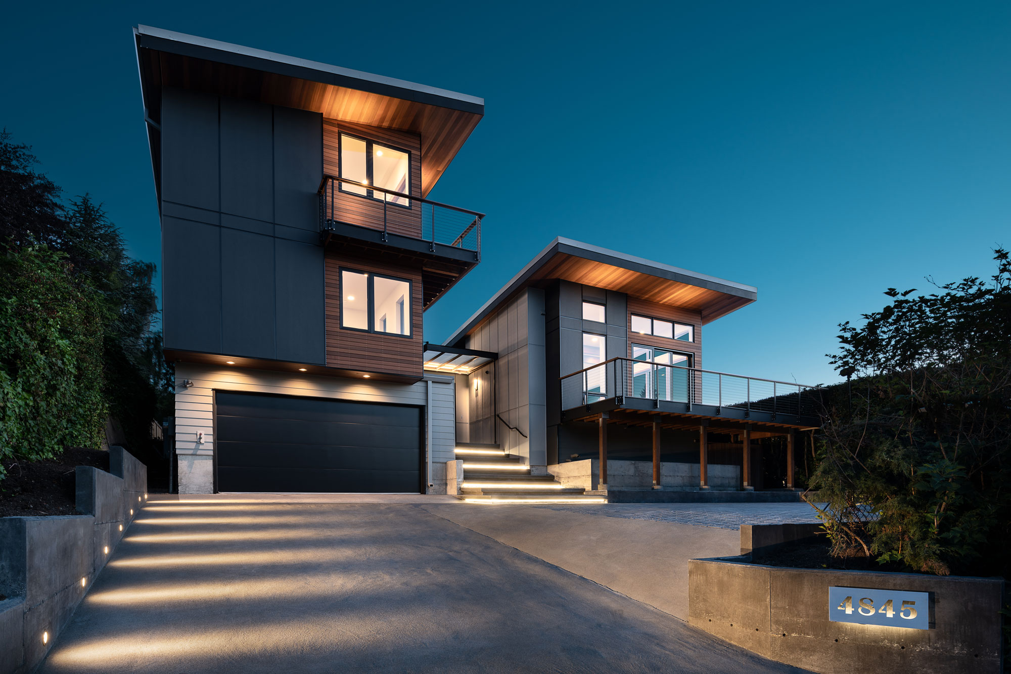 three story dark brown colored wood and steel metal modern house with glass windows garage and driveway