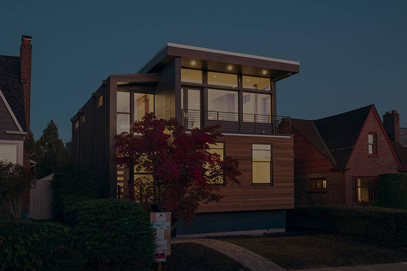 two story dark brown colored wood roosevelt modern house with wide glass windows
