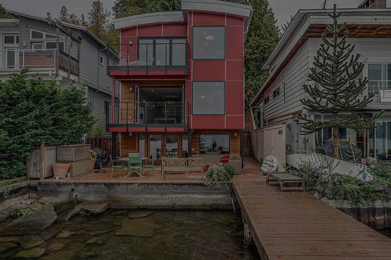 brick-red three story washington lake house with wooden deck