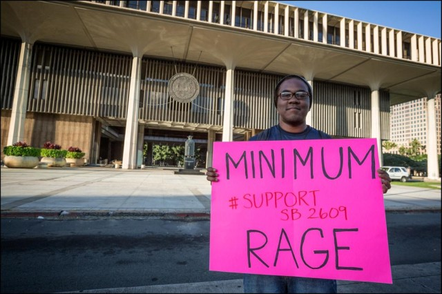 A protester at the Hawaii State Capitol urges lawmakers to raise the minimum wage during the 2014 legislative session.