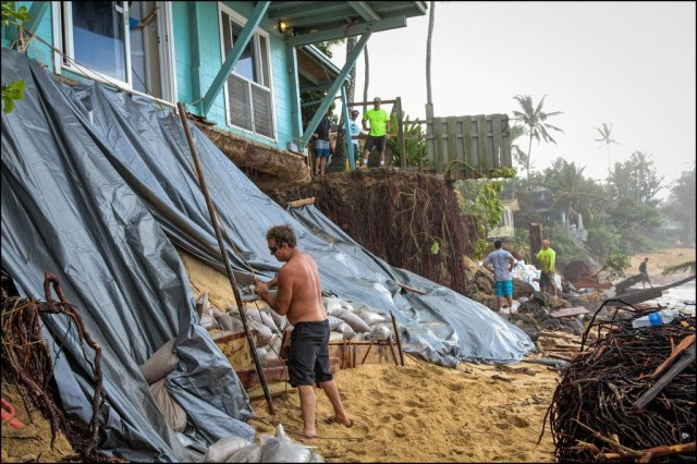 A man battles coastal erosion outside a residence on the North Shore.