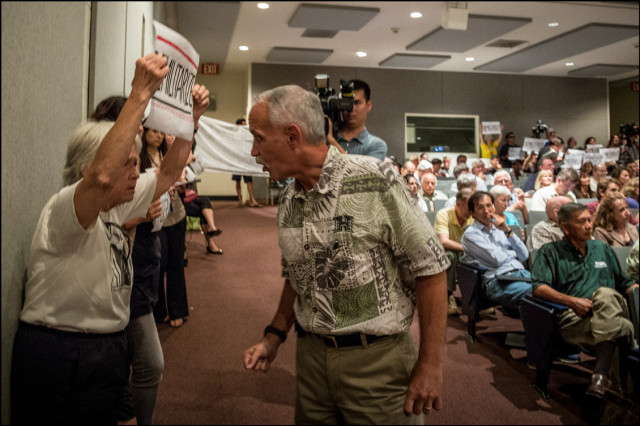 UH Manoa Chancellor Tom Apple asks a shouting protestor to please let Lt. General Francis Wiercinski  speak without interruption during his public presentation at the UH Architecture Auditorium on May 6, 2014.