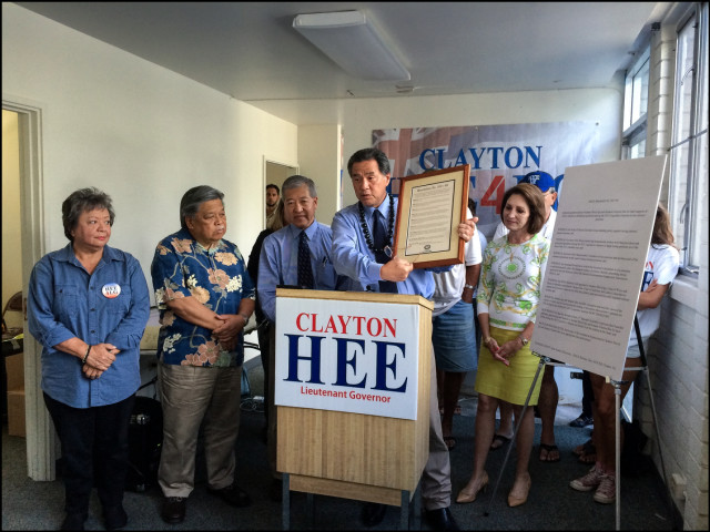 At a news conference in his campaign headquarters on August 1, 2014, Sen. Clayton Hee holds up a resolution from HGEA expressing gratitude to Sen. Hee for his blocking a pension tax on seniors.
