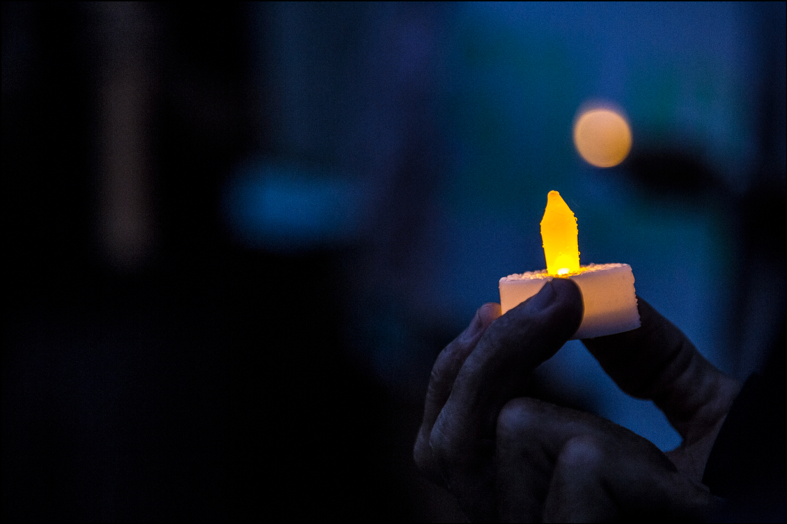 Highlights of HECO's plans, to be achieved by 2030, include at least 65 percent renewable energy, reducing electric bills by 20 percent and nearly tripling the amount of distributed solar power. But dozens of protestors, like the one who brought this LED candle to the evening protest, have deep doubts about the company.