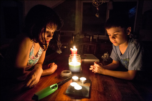 Cali and Lucas Lucero their house after dark without electricity in Puna on August 12, 2014.