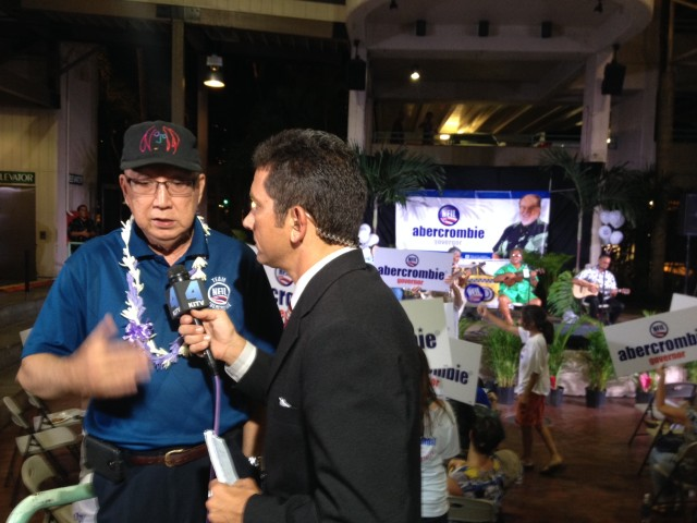 Randy Iwase, left, a longtime friend of Gov. Neil Abercrombie, speaks to KITV reporter Andrew Perreira after polls closed for the primary election last year. Now, as PUC chair, Iwase is in the thick of a public debate with higher stakes than most elections.