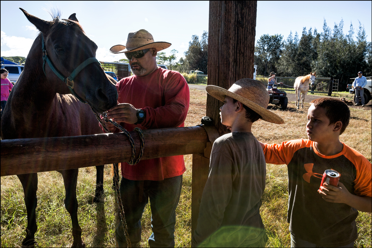Cy Haumea shows his son, Cameron (in hat) and a friend the proper way to tie up a horse.