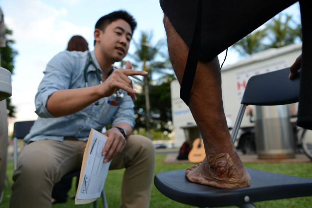 University of Hawaii John A. Burns third year medical student Princeton Ly examines Junior's infected left ankle during volunteer outreach work with the Hawaii Home Project at Kakaako Park.  9 October 2014. photograph by Cory Lum