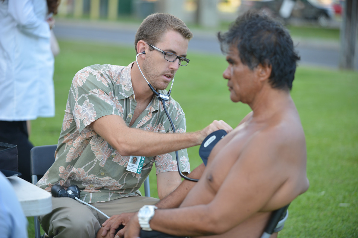 University of Hawaii John A. Burns Medical school student Harry Wynn-Williams takes blood pressure of a patient  (gave name as Junior) during volunteer outreach work  near Kakaako Park.  9 October 2014. photograph by Cory Lum