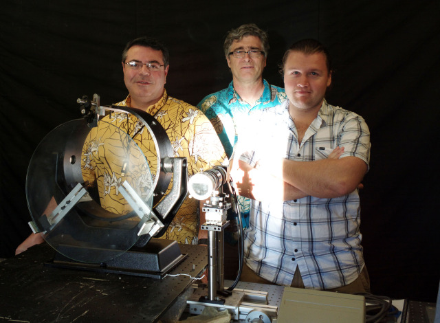 The MorphOptics team, from left, Dr. Joe Ritter, Dr. Jeff Kuhn, and Ian Cunnyngham, stand behind a mirror fabricated using the high-quality/low-cost shaping process that they developed at UH's Institute for Astronomy, and that they are now trying to turn into a business at XLR8UH.
