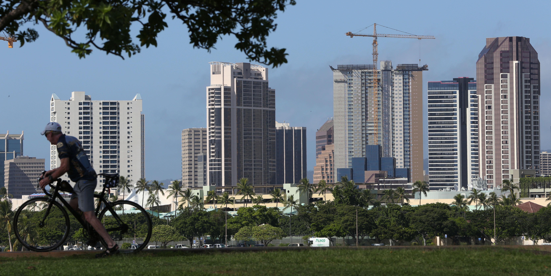 Construction cranes against backdrop of condominium buildings in Kakaako. Honolulu, Hawaii.  20 nov 2014. photo Cory Lum.