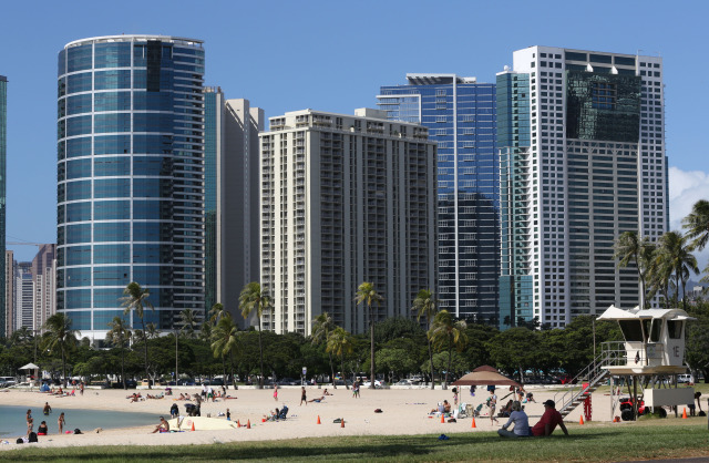 Towering building with beachgoers enjoying the hot weather today.