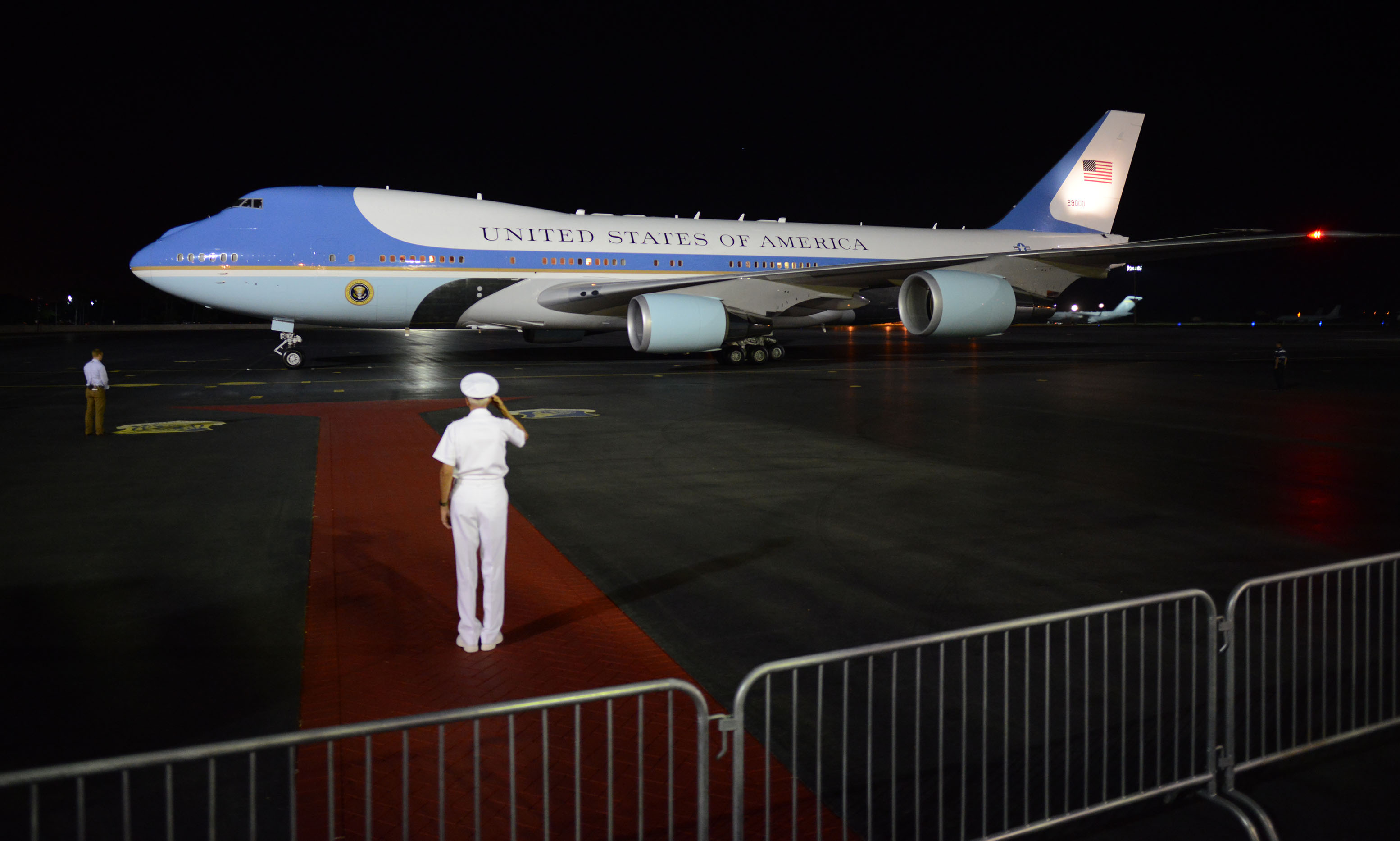 Admiral Samuel Locklear III, commander of U.S. Pacific Command, salutes as Air Force One arrives.
