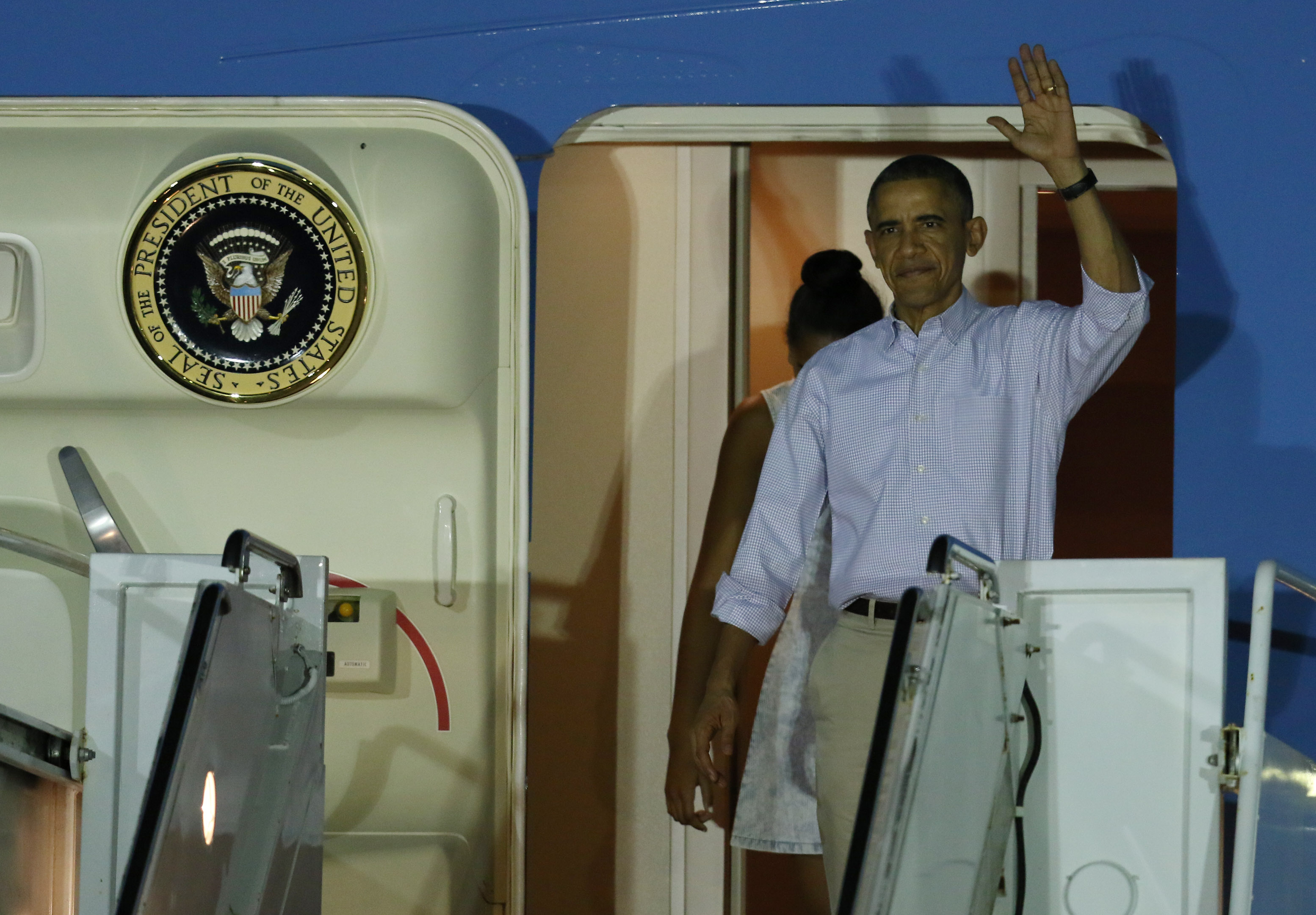 President Barack Obama waves as he exits Air Force One on Friday night.
