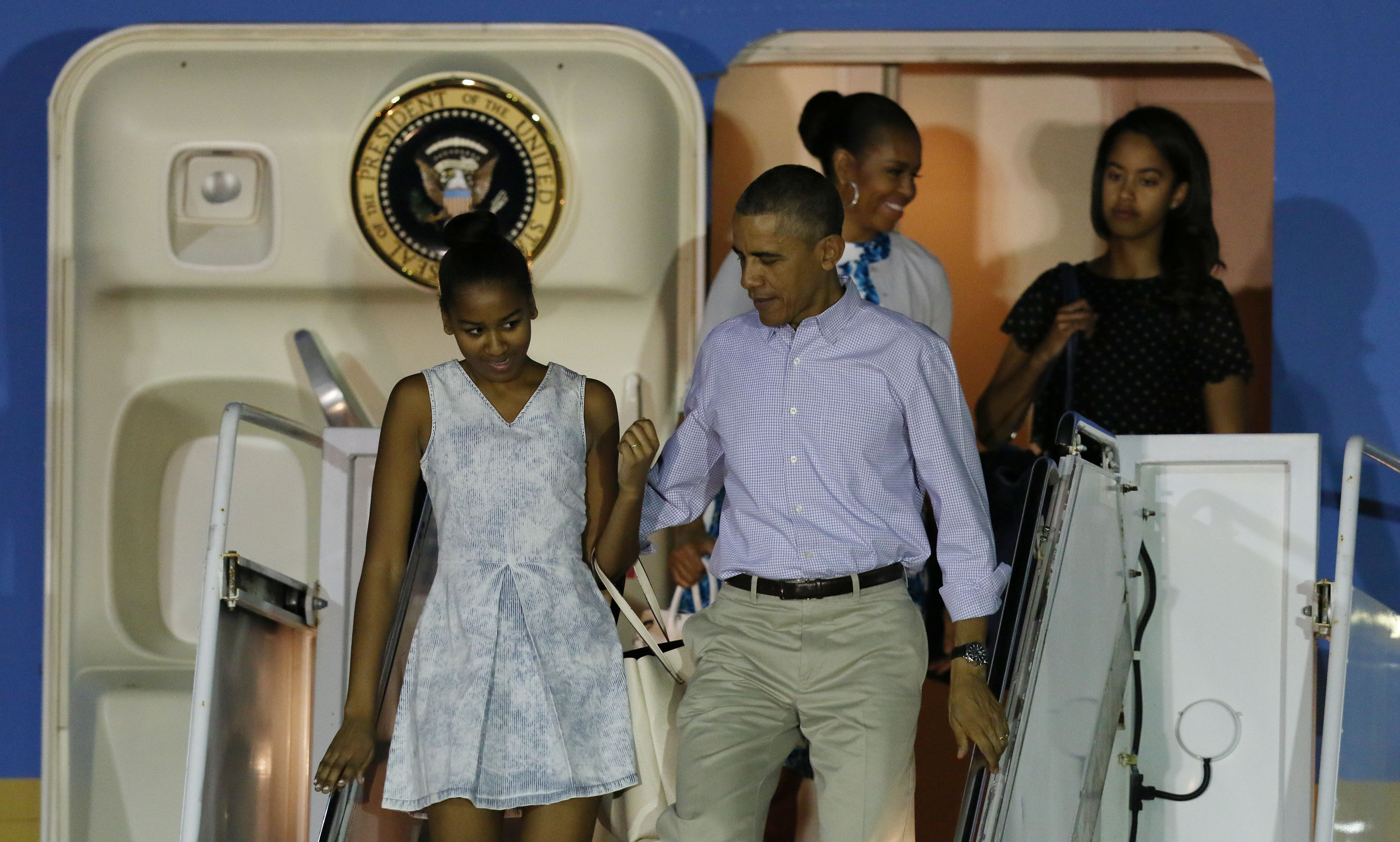 President Obama and his daughter Sasha descend the stairs, followed by First Lady Michelle Obama and daughter Malia.