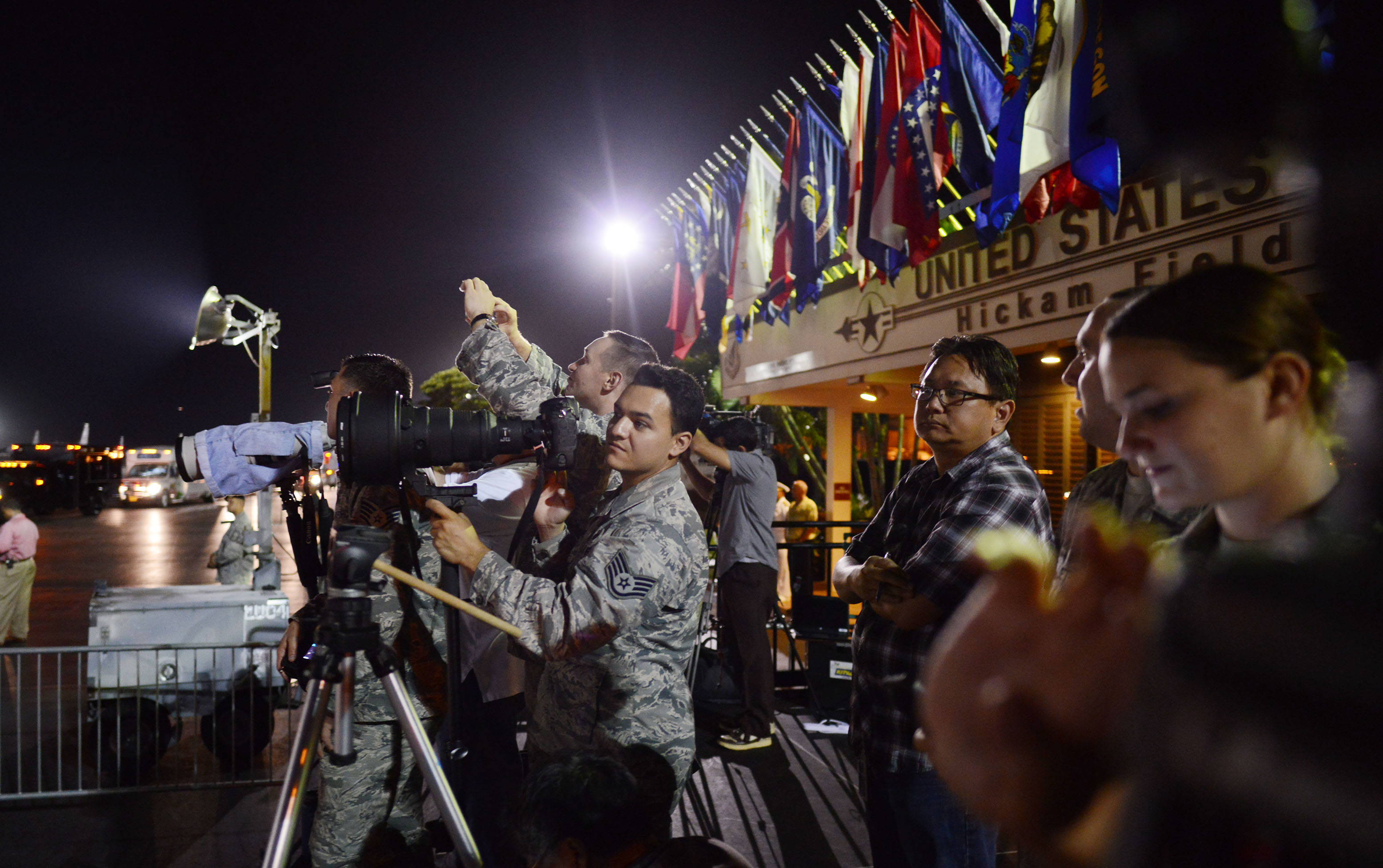 Military photographers and members of the media watch the arrival of Air Force One.