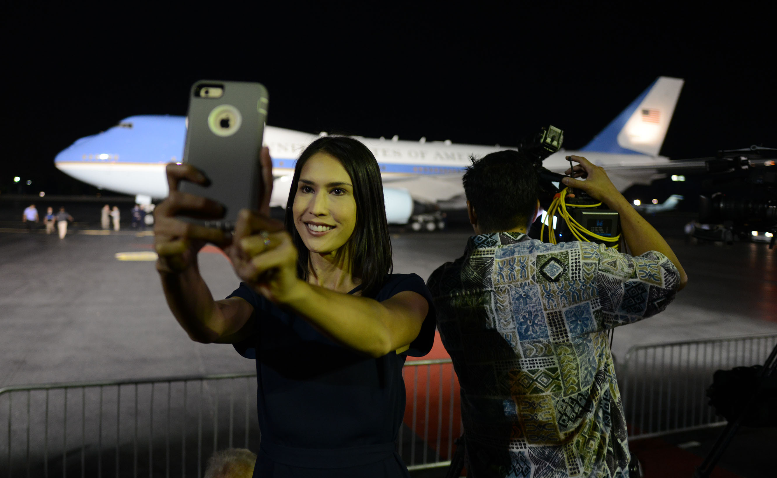 <p>Members of the local media on hand for presidential arrivals and/or departures sometimes shoot selfies during their down time. KHON reporter Sarah Yoro captures herself with Air Force One in the background on Dec. 19, 2014.</p>
