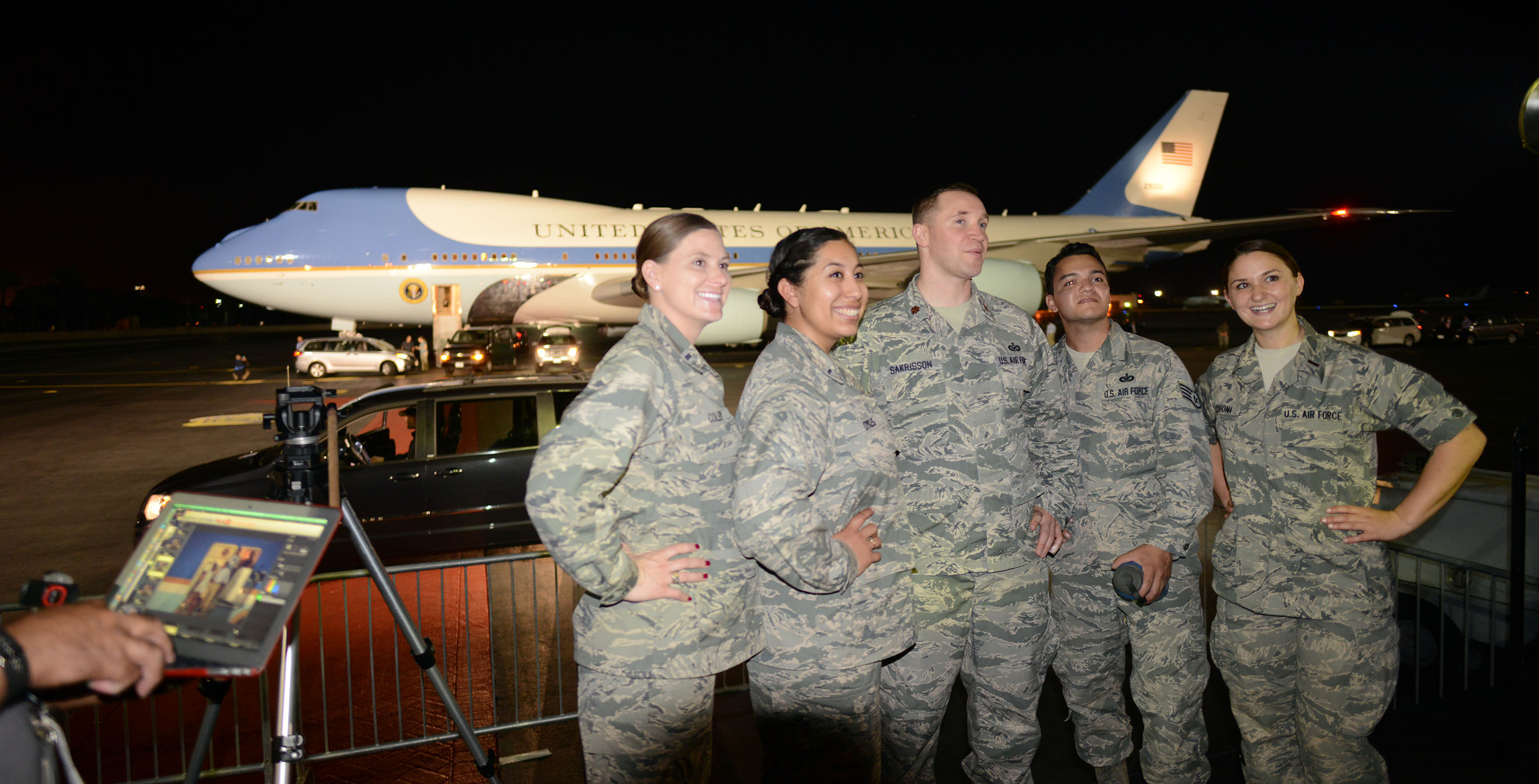 Air Force personnel pose for photographs in front of Air Force One.