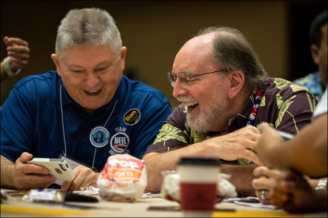 Gov. Neil Abercrombie and John Radcliffe, president of Capitol Consultants of Hawaii, share an iPhone moment during a recess in second day of the Democratic Party of Hawaii State Convention. 5.25.14©PF Bentley/Civil Beat
