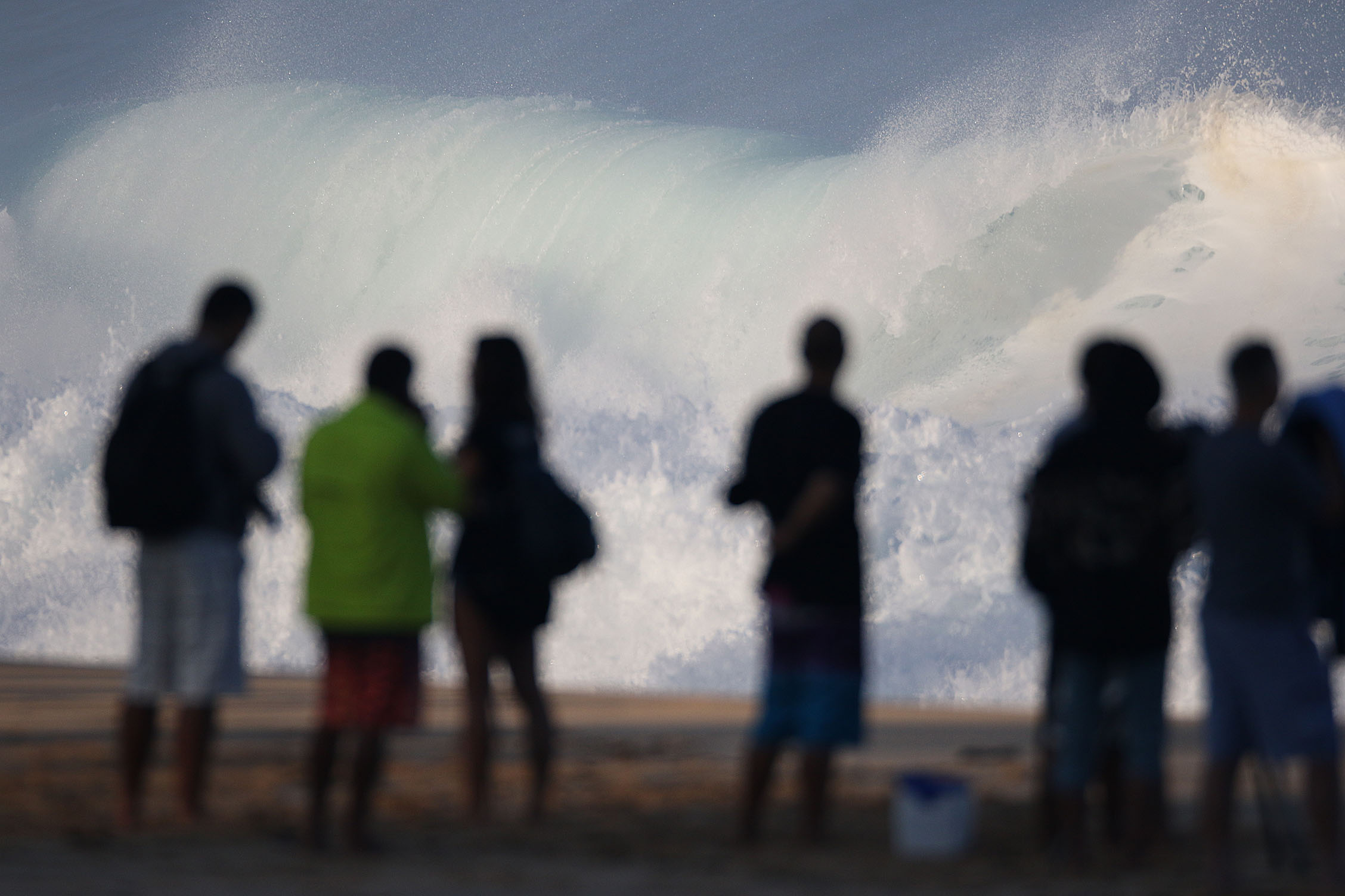<p>Beachgoers watch the large surf at the Banzai Pipeline. Winter waves are sometimes so epic you&#8217;d think the hazards are obvious, but lifeguards issue plenty of warnings anyway.</p>