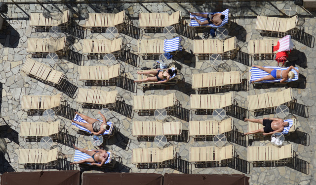 Visitors enjoy the sun on deck at Ohana Waikiki West pooliside recliners. 2 dec 2014. photograph cory Lum
