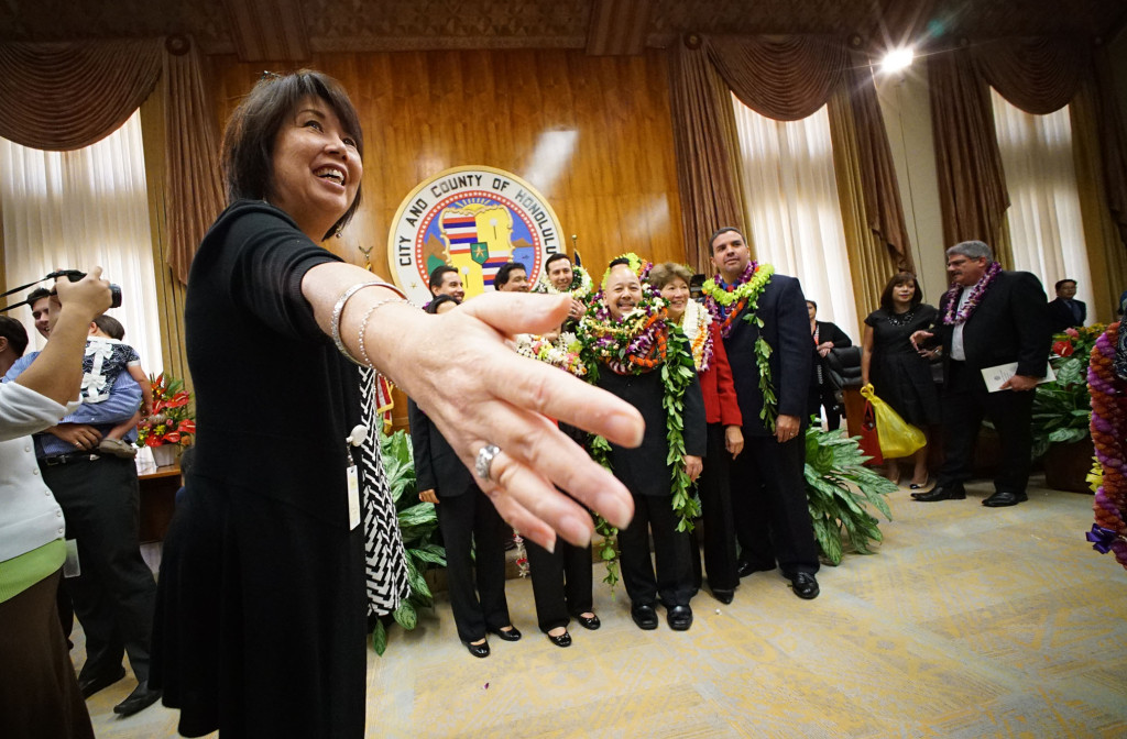 Members of the Honolulu City Council gather for a group photograph as a staff member holds their hands up to form a barrier after oath of office ceremonies.  2 jan 2015. photograph Cory Lum