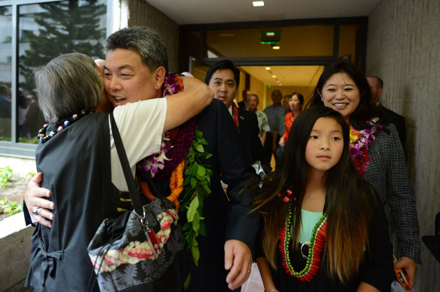 Representative Mark Takai receives a lei and hug from a wellwisher after oath of office ceremonies held at the Federal Building. 16jan2015. photograph Cory Lum/Civil Beat