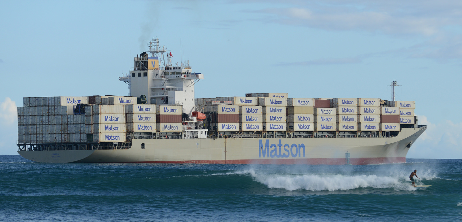 Matson container ship leaves Honolulu Harbor as surfers ride waves. sept 2014. photograph Cory Lum/Civil Beat