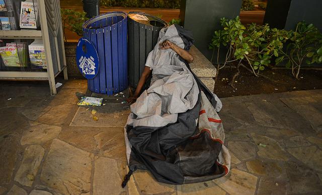Tarp covered man as he rests along Kalakaua Avenue. 9 jan 2015. photograph Cory Lum/Civil Beat