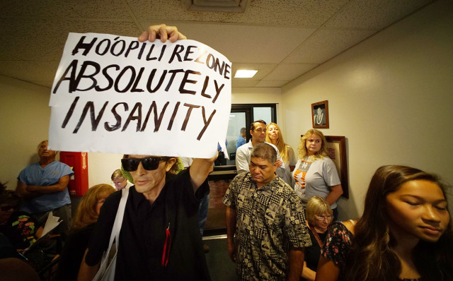 Honolulu resident David Gonzales holds a sign during Hoopili hearing at the city council  5 march 2015. photograph Cory Lum/Civil Beat