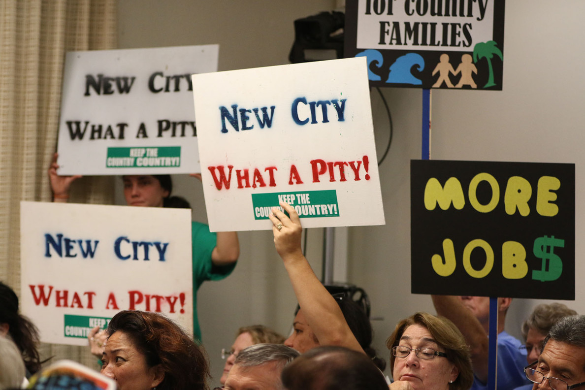 Supporters hold signs during hearing about Malaekahana development.  5 march 2015. photograph Cory Lum/Civil Beat