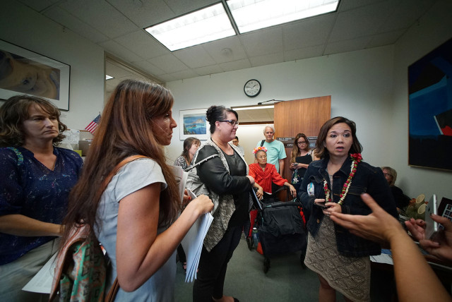 Ways and Means chair Senator Jill Tokuda makes her way thru to her office as supporters of SB1037 sit in the hallway fronting her office.  3 march 2015. photograph Cory Lum/Civil Beat