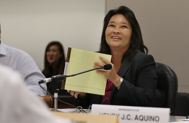 House Finance Chair Sylvia Luke jokes around by holding large notepad to block out people reading her lips before joint conference committee meeting. 23 april 2015. photograph by Cory Lum/Civil Beat