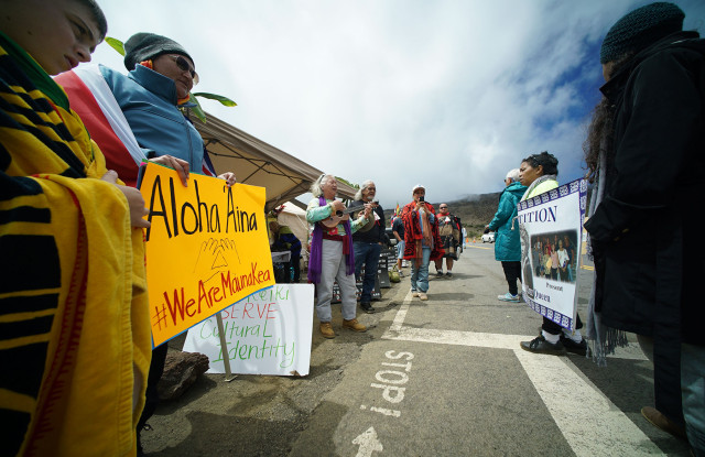 Demonstrators stand across the Mauna Kea visitors center with signs in support of stopping the Thiry Meter Telescope project on Mauna Kea.  9 apr 2015. photograph Cory Lum/Civil Beat