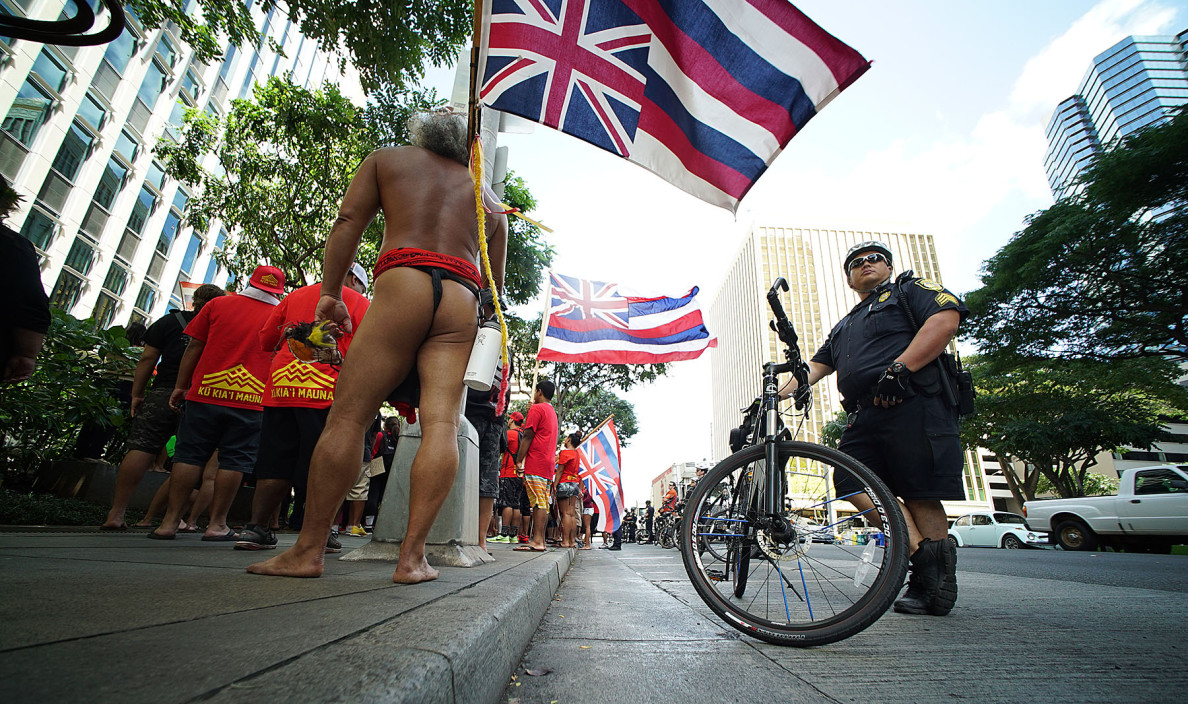 Demonstrators stop at the First Hawaiian Bank tower to deliver petition to the law offices of Watanabe and Ing on their way to visit the Governor's office. 21 april 2015. photograph Cory Lum/Civil Beat