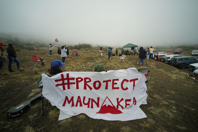 Supporter sing as fog rolls near the Mauna Kea visitors center. 10 april 2015. photograph Cory Lum/Civil Beat