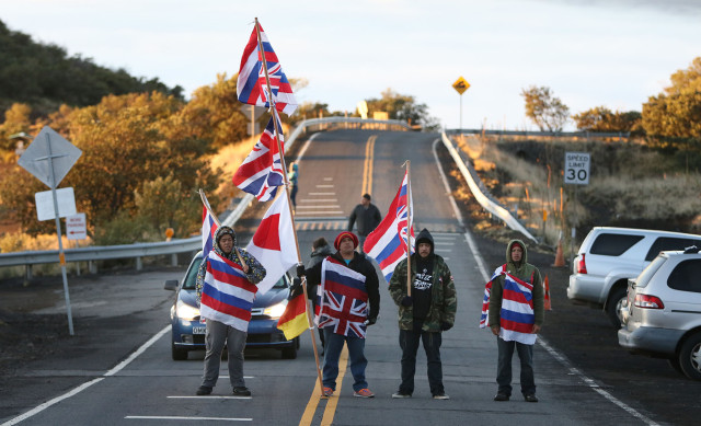 Supporters draped in the Hawaiian flags chant as they approach the Mauna Kea visitor center.  10 april 2015.  photograph by Cory Lum/Civil Beat